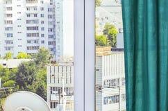 Grön gardin på ett dekorativt fönster med ett foto av gatan arkivbild