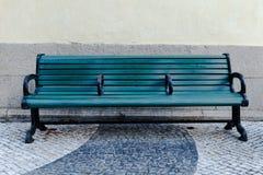 Grön gatabänk på trottoaren Royaltyfria Bilder