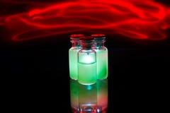 Grön glödande medicin med brand Arkivfoton
