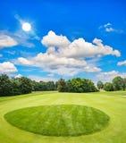 Grön golfbana och blå solig himmel arkivfoton