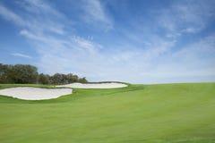Grön golffarled med sandfällor nedanför blå himmel med moln Arkivfoton