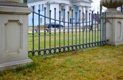 Grön gräsmatta framme av ett dekorativt staket med stänger, bakgrund Härligt bearbetat staket Bild av ett dekorativt gjutjärnstak Royaltyfria Bilder