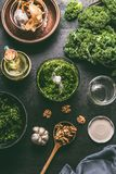 Grön grönkålpesto i blandare på mörk lantlig köksbordbakgrund med ingredienser, bästa sikt Grönkålpestoförberedelse Sunt fotografering för bildbyråer