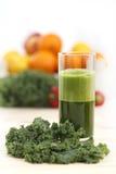 Grön grönsakfruktsaft i ett högväxt exponeringsglas med ett blad av grönkål Arkivfoto