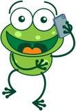 Grön groda som talar på en smartphone Arkivbild