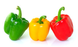 Grön gul röd peppar på vit bakgrund Fotografering för Bildbyråer