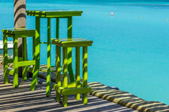 Grön hög tabell med två stolar med det blåa havet som bakgrund Arkivfoton
