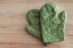 Grön handske på en trätabell Arkivbilder