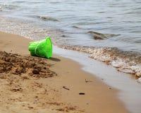 Grön hink på sanden på en suny stranddag Arkivfoto