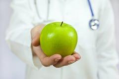 grön holding för äppledoktor Royaltyfri Foto
