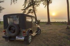 Grön indier SUV på torrt gräs mot bakgrunden av träd och solnedgången över havet fotografering för bildbyråer