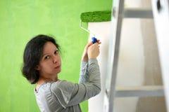 Grön innervägg för nätt målning för ung kvinna med rullen i ett nytt hem royaltyfri fotografi