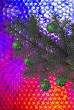 Grön julgran med julbollar på en gladlynt mång--färgad bakgrund fotografering för bildbyråer