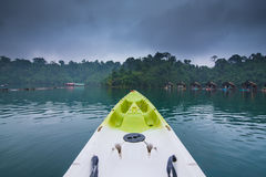 Grön kajak på morgon efter regn i en nat sjöskog och flod Arkivbild