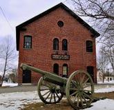 Grön kanon framme av en gammal tegelstenbyggnad på en gräsplan i stad Royaltyfri Fotografi