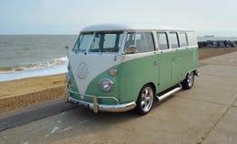 Grön klassiker och vit VW-campareskåpbil som parkeras på sjösidapromenad arkivbild