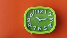 Grön klocka med vitnummer och pilar på orange bakgrund, Tid schackningsperiod lager videofilmer
