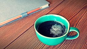 Grön kopp & anteckningsbok på wood bakgrund Fotografering för Bildbyråer