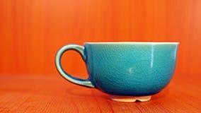 Grön kopp på wood bakgrund Arkivfoto