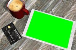 Grön kreditkort och kopp kaffe för skärmminnestavlaPC Arkivfoton