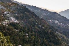 Grön kulle nära det Kangchenjunga berget med moln över, träd och byn med solljus som beskådar i aftonen i norr Sikkim Royaltyfria Bilder