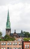 Grön kyrktorn utöver gamla tegelstenbyggnader Royaltyfri Bild