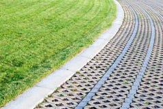 Grön Lawn med Pebbles och belägger med tegel arkivbild