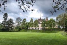 Grön lekplats med gamla byggnader Arkivfoton