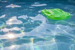 Grön lifesaver som svävar i en simbassäng Arkivbilder