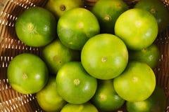 Grön limefrukt i korg Fotografering för Bildbyråer