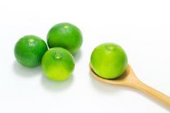 Grön limefrukt i träskeden som isoleras på vit bakgrund Arkivbild