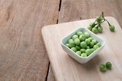 Grön liten aubergine på den vita plattan, asiatiska matingredienser Arkivbilder