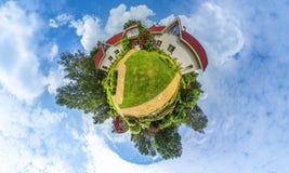 Grön liten planetpanorama med arkitektur och träd, mjuk blå himmel och vit fördunklar Byggnader på sommar Sommar Royaltyfri Bild