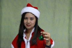 Grön magisk boll på handen av asiatet Santa Girl Dress på ljus - grön bakgrund royaltyfria bilder