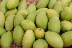 Grön mangofrukt en bambukorg Royaltyfri Foto