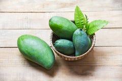Grön mangosommarfrukt och gröna sidor i korgen på träbakgrund - ny rå mango royaltyfria foton