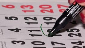 Grön markörcirkel två dagar på pappers- kalender Planläggningsaffärsmöte lager videofilmer