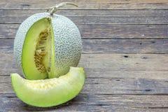 Grön melon som skivas på trätabellen arkivbild