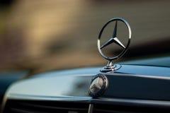 Grön Mercedes-Benz för gammal sällsynt tappning huv, emblem, elementskyddsgaller på suddig bakgrund Symbolet av rikt liv royaltyfria bilder
