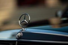 Grön Mercedes-Benz för gammal sällsynt tappning huv, emblem, elementskyddsgaller på suddig bakgrund Symbolet av rikt liv royaltyfri foto