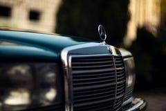 Grön Mercedes-Benz för gammal sällsynt tappning huv, emblem, exponeringsglas, billyktor, elementskyddsgaller på suddig bakgrund arkivfoto