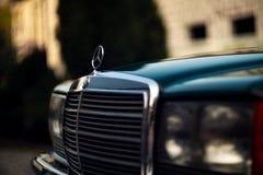 Grön Mercedes-Benz för gammal sällsynt tappning huv, emblem, exponeringsglas, billyktor, elementskyddsgaller på suddig bakgrund arkivbild