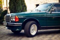 Grön Mercedes-Benz för gammal sällsynt tappning huv, hjul, dörr, vindruta, spegel, emblem, exponeringsglas, billyktor, elementsky royaltyfri foto