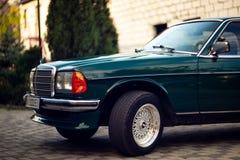 Grön Mercedes-Benz för gammal sällsynt tappning huv, hjul, dörr, vindruta, spegel, emblem, exponeringsglas, billyktor, elementsky royaltyfri bild