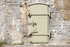 Grön metalldörr i den gamla väggen, bakgrundstextur Royaltyfria Foton