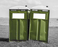 Grön mobil toalett på en svartvit strand Royaltyfri Fotografi