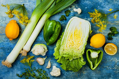 Grön och gul veggiesgrupp Vegetariska matställeingredienser Grön grönsakvariation Över huvudet plan lekmanna- bästa sikt royaltyfri foto