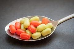 Grön och orange godis. Arkivfoton