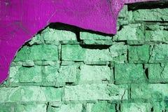 Grön och purpurfärgad tegelstenvägg arkivfoton