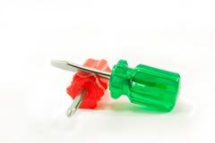 Grön och röd skruvmejsel som isoleras på vit Arkivfoton